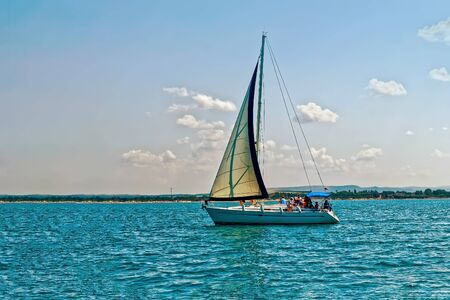 Summer Sunny day on the Black sea. People relax on a pleasure yacht. A sailing boat is drifting in the sea. Beautiful summer seascape.