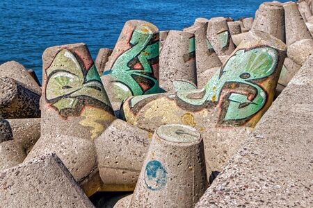 Colorful graffiti on the breakwaters against the blue sea
