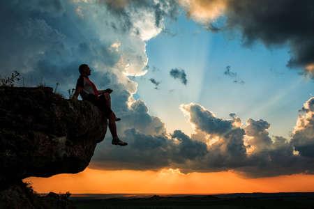 personas sentadas: hombre sentado en la parte superior de piedra de alta montaña en la puesta del sol