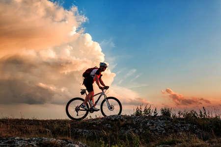 andando en bicicleta: Biker montar en bicicleta en las montañas en la puesta del sol