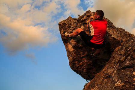 escalando: escalada escalador en roca. Escalador masculino fuerte con espacio de copia Foto de archivo