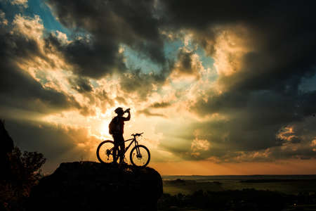 high mountain: Silhouette of a biker drinking from bottle on sunset