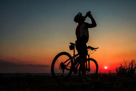 Silhouette of a biker drinking from bottle on sunset