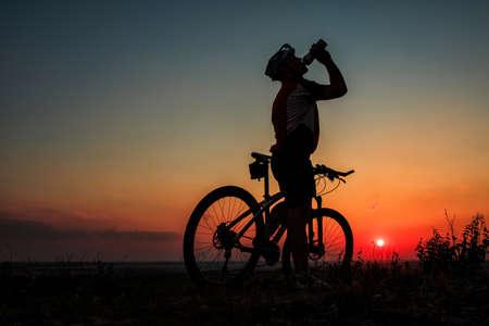 Silhouette eines Biker von der Flasche trinkt auf Sonnenuntergang Standard-Bild - 42787124