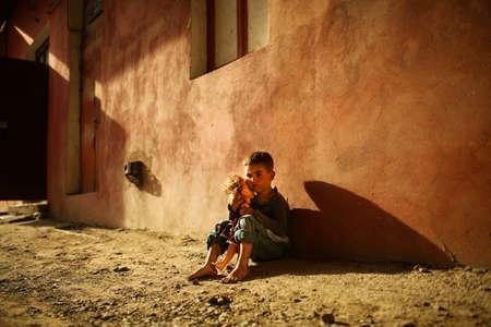 niños sentados: solo triste niño jugando en una calle