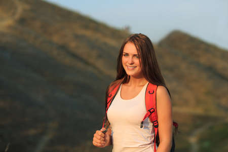 sportswoman: Happy sportswoman with red backpack walking on sunset summer.