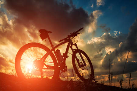 Beautiful scene of bike on sunset in mountains with deep clouds