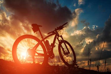 Schöne Szene des Fahrrad auf Sonnenuntergang in den Bergen mit tiefen Wolken Standard-Bild - 44345762