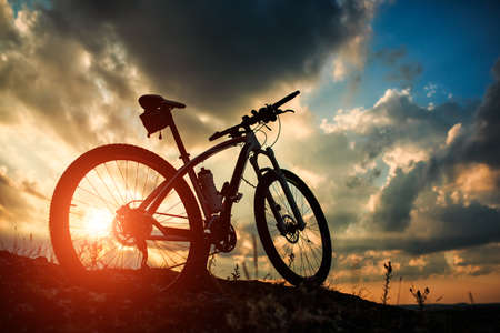 Beautiful scene of bike on sunset in mountains with deep clouds Stok Fotoğraf - 44670791