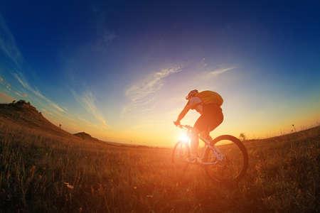 andando en bicicleta: Silueta de una bicicleta en el fondo del cielo en la puesta del sol Foto de archivo
