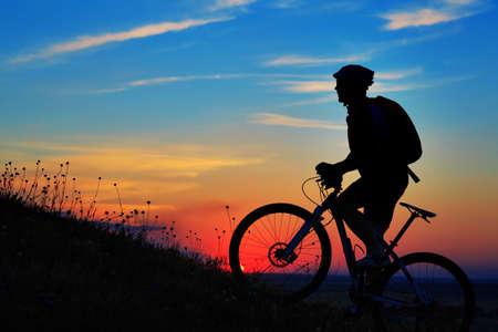 Silhouette eines Fahrrades am Himmel Hintergrund auf Sonnenuntergang Standard-Bild - 44957569