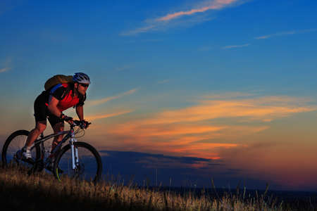 adventure holiday: Silhouette of a bike on sky background on sunset Stock Photo