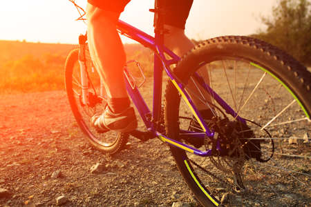 bike: low angle view of cyclist riding mountain bike on rocky trail at sunrise