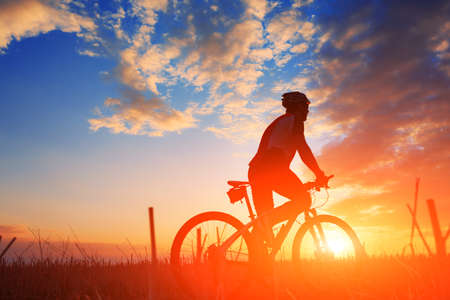 Silhouette of a bike on sky background on sunset Imagens