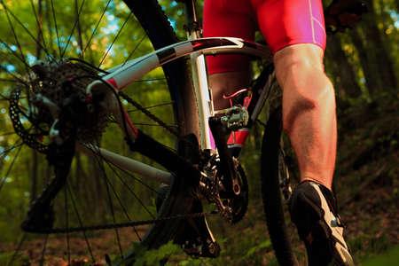 Radfahrerreiten auf dem Fahrrad im Wald auf Sonnenuntergang Standard-Bild - 45688366