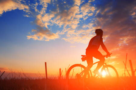 mountain bicycle rider on the hill with sunrise background Stockfoto