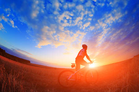 mountain bicycle rider on the hill with sunrise background Standard-Bild