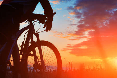 Silhouette of a bike on sky background on sunset Foto de archivo
