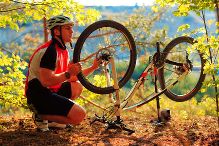 cycler: Man cyclist repairing a bike  against the background of blue sky at afternoon