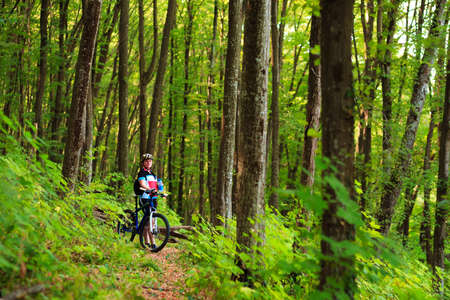 aim: Female tourist and bicycle enjoying wood view
