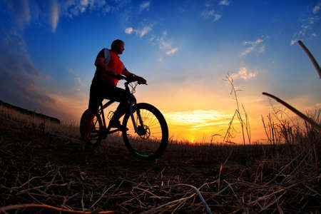 rapidity: Silhouette of a man on muontain-bike, sunset Stock Photo
