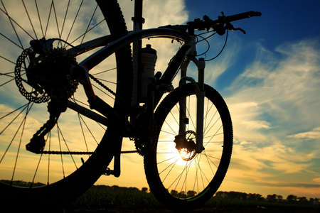 road cycling: bicycle on a road against sunset. travel concept