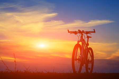 romance: Fim bonito acima da cena de bicicleta ao pôr do sol, silhueta da bicicleta para a frente ao sol, maravilhoso cenário rural, Banco de Imagens