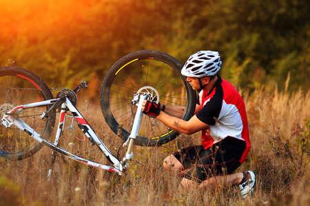 Bike repair. Young man repairing mountain bike in the forest
