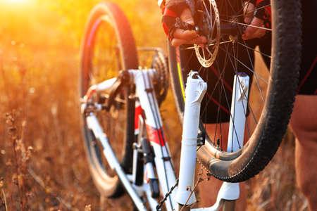 cadena rota: Reparación de bicicletas. Joven reparación de bicicleta de montaña en el bosque Foto de archivo