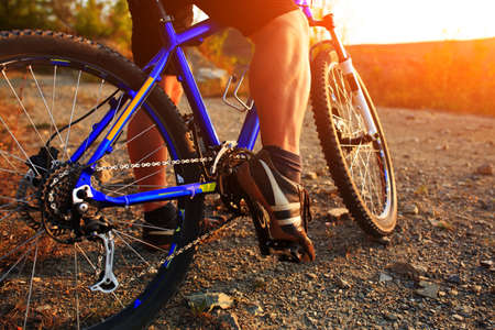 Detail of cyclist man feet riding mountain bike on outdoor trail on country road