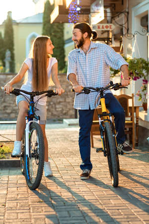bicyclists: Portrait of happy young couple of bicyclists talking in the street