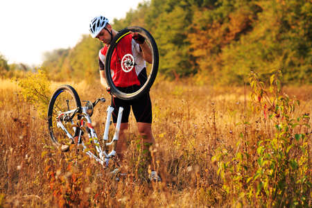 cycler: cyclist repairing a bike  against green nature in summer on a sunny day at afternoon