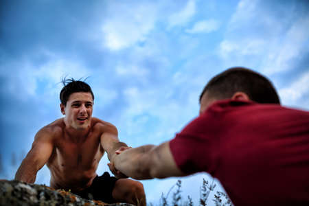 The Muscular rock climber gives hand for help to the partner Stockfoto