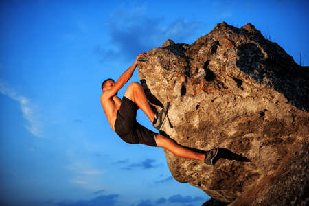 alpinism: Muscular Climber climbs on a cliff with blue sky on background Stock Photo