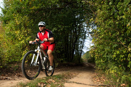 road cycling: Biker on the forest road riding outdoor in sunny autumn day