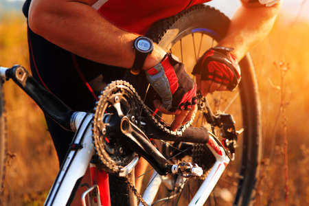 cadena rota: Ciclista del hombre la reparación de su ciclo en el prado soleado