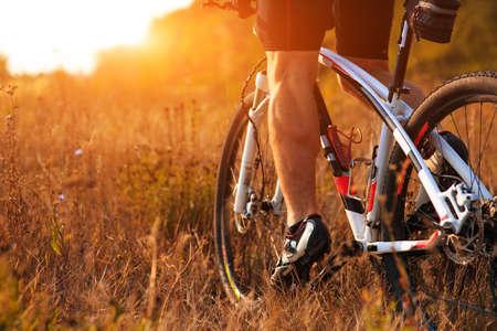 piernas hombre: Primer plano de las piernas del hombre Ciclista que monta en bicicleta de montaña en rastro al aire libre en el bosque de otoño Foto de archivo