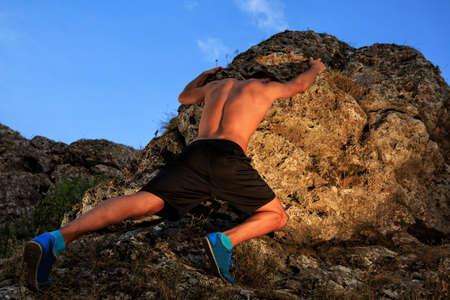 steiermark: Young man climbing the mountain ridge on sunset Stock Photo