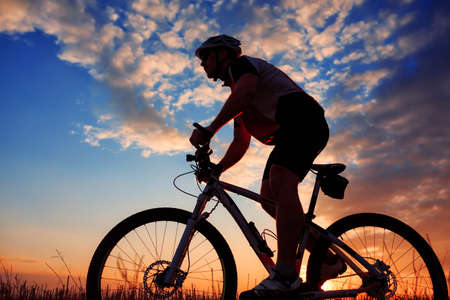 rapidity: Silhouette of mountain biker against sunrise with clouds