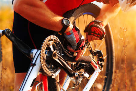 sports gear: image of cyclist repairs bicycle on the meadow Stock Photo