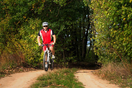 daredevil: Man cyclist is cycling in autumn forest