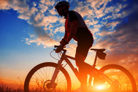 outdoors woman: Silhouette of a biker in autumn on a sunny afternoon against blue sky
