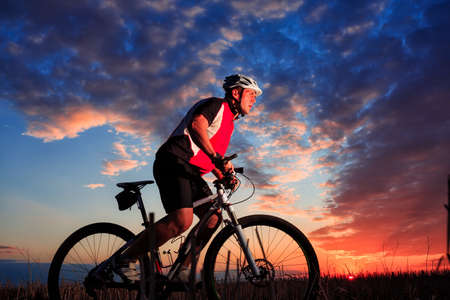 rapidity: Silhouette of a bike on sky background on sunset Stock Photo