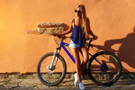 old school bike: Pretty young hipster blonde girl posing outdoor against wall with sport bicycle nice colors sunset