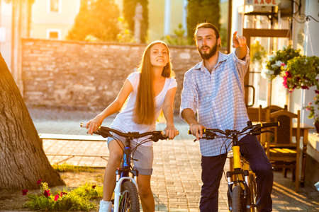bicyclists: Portrait of happy young couple of bicyclists smiling in the street Stock Photo