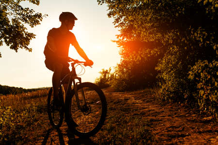 rapidity: Silhouette of a biker on sky background on sunset with focus on bike Stock Photo