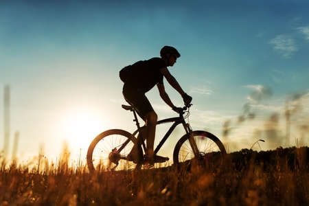 Cyclist rides on a meadow against blue sky