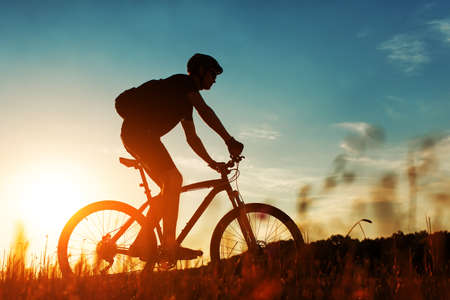 mountain bicycling: Cyclist rides on a meadow against blue sky