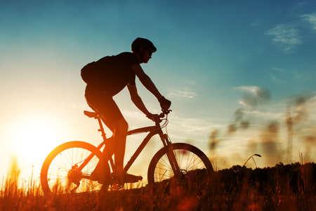 ciclismo: paseos ciclista en un prado contra el cielo azul