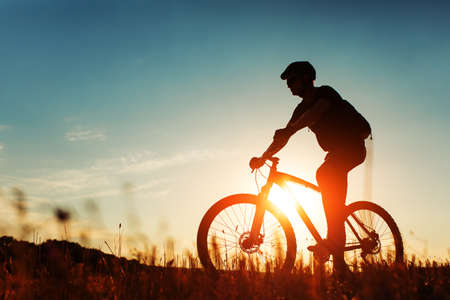 red mountain: Silhouette of a biker on sky background on sunset with focus on bike Stock Photo